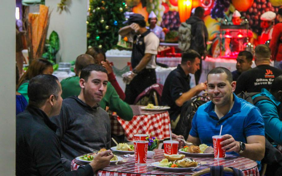 Servicemembers enjoy a Christmas Day meal prepared by Navy Morale, Welfare and Recreation at the U.S. Navy base in Bahrain.