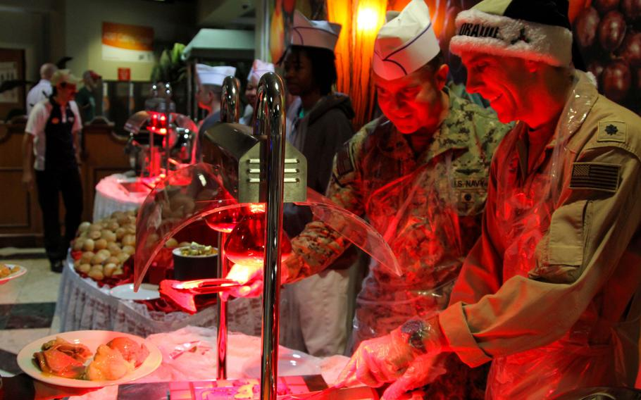 Naval Support Activity Bahrain commander Capt. David Meron, left, and the base executive ,Cmdr. Leif Hammersmark, serve food at a special Christmas meal for servicemembers.