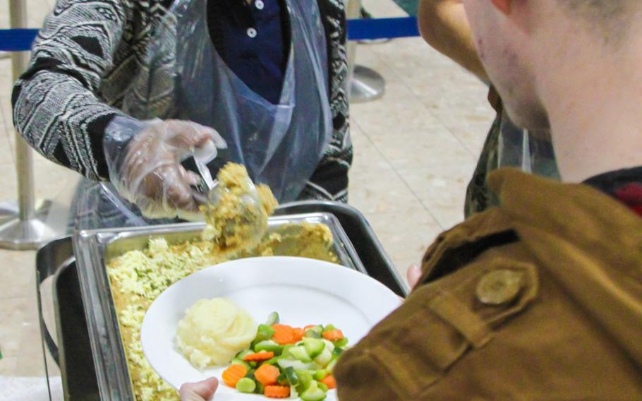 Chief Warrant Officer 3 Renee Wright serves food at a Christmas meal for servicemembers at the U.S. Navy base in Bahrain.