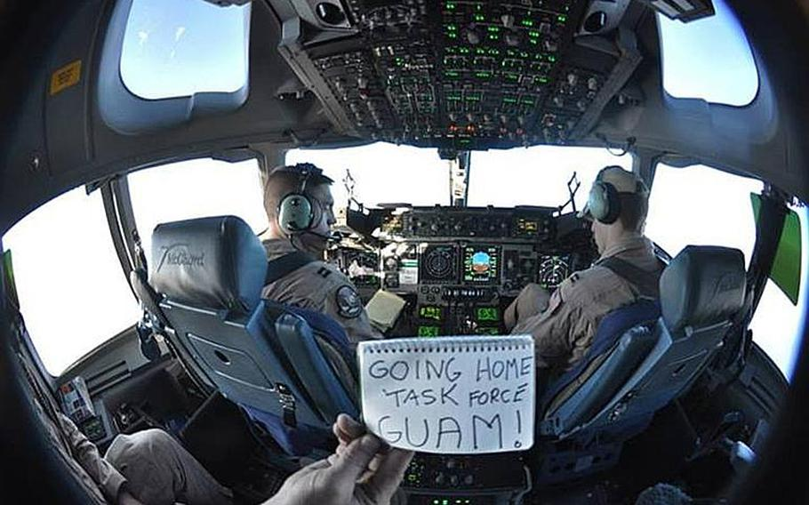 """Capt. Brandon Leigh, left, and Capt. Jeff Pecora of the 817th Expeditionary Airlift Squadron Detachment 1 based out of Manas Transition Center, Kyrgyzstan, pilot a C-17 Globemaster III carrying about 150 troops from 1st Battalion, 294th Infantry Regiment, Guam Army National Guard, from Kabul, Afghanistan. Holding the """"Going Home Task Force Guam"""" sign is Air Force Staff Sgt. Jeremy Nallay."""