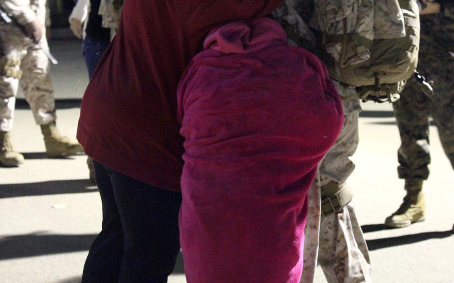 Maj. Erich Schloegel hugs his wife, Christa, and daughters Lily (in pink blanket) and Emme goodbye at Camp Pendleton, Calif., before leaving for a yearlong deployment to Afghanistan with I Marine Expeditionary Unit (Forward).