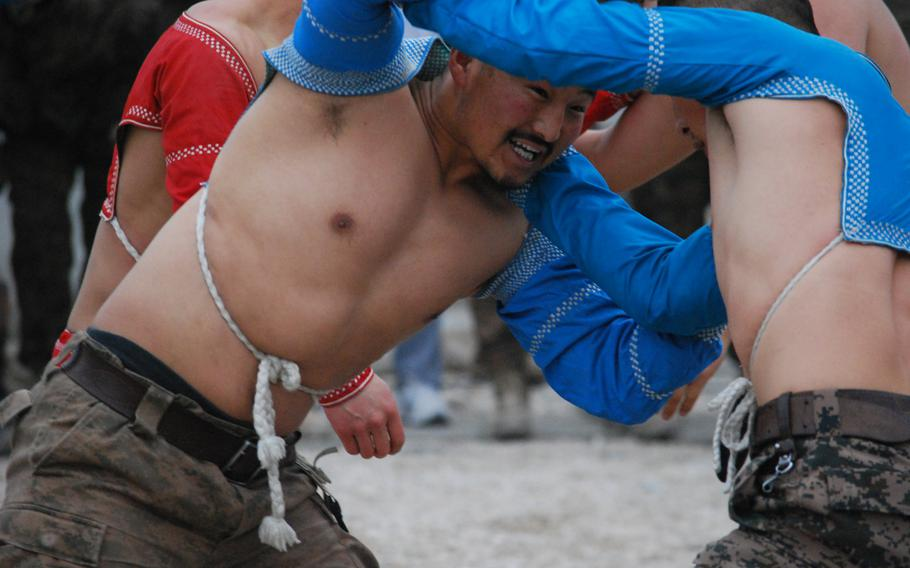 Two soldiers with the Mongolian Armed Forces contingent based at Camp Marmal in Mazar-i-Sharif, Afghanistan, wrestle in their annual Lunar New Year tournament, Jan. 31, 2014. Wrestling, a popular tradition in Mongolian culture, is used to bring in their new year.