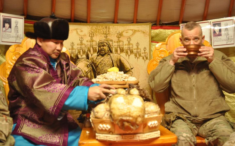 U.S. Army Col. Wallace Steinbrecher, garrison commander for Camp Marmal Regional Command North, sits with a Mongolian soldier in his traditional wardrobe as he serves his coalition counterparts traditional Mongolian tea and a lamb dish prepared to bring in the new year.