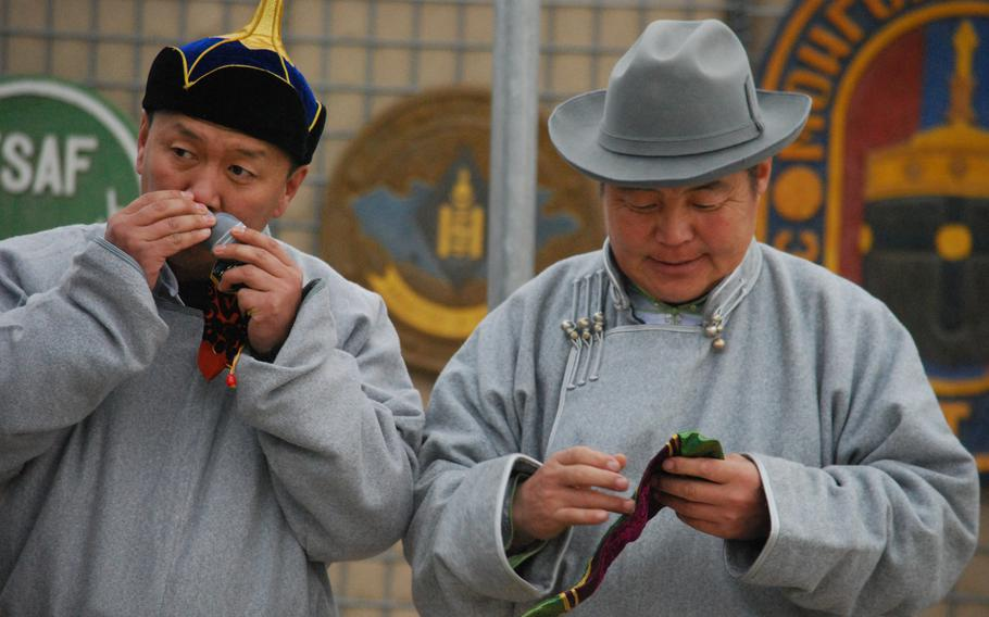Two Mongolian soldiers dressed in traditional Mongolian garb smell an incense that was prepared for the Lunar New Year celebration at Camp Marmal in Mazar-i-Sharif, Afghanistan, Jan. 31, 2014.