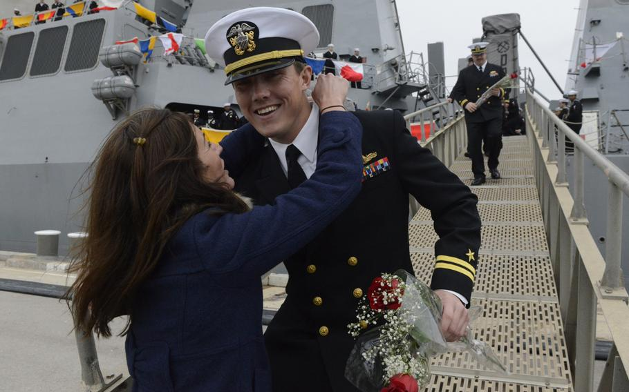 An officer assigned to the guided-missile destroyer USS Donald Cook is greeted at the gangplank as the ship arrives in Rota, Spain, on Tuesday, Feb. 11, 2014.