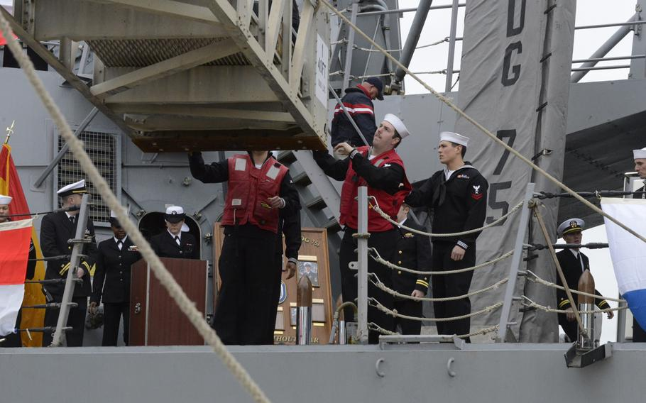 Sailors aboard the guided-missile destroyer USS Donald Cook lower the gangplank as the ship arrives in Rota, Spain, on Tuesday, Feb. 11, 2014. Donald Cook is the first of four Arleigh Burke-class guided-missile destroyers to be stationed in Rota.