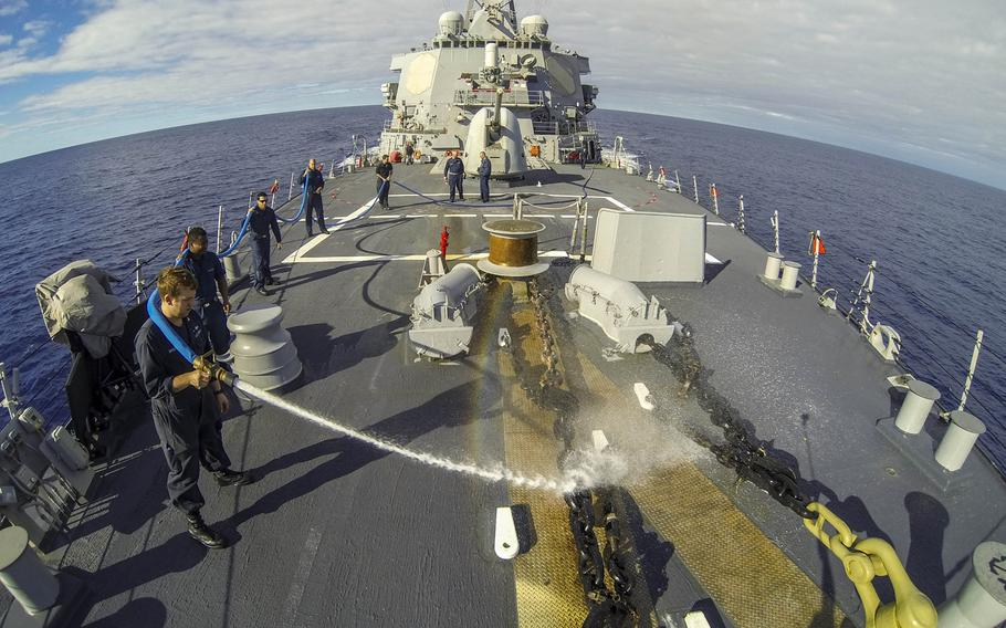 Sailors wash down the Arleigh Burke-class guided-missile destroyer USS Donald Cook while it was en route to Rota, Spain, where it arrived on Tuesday, Feb. 11, 2014, as the first of four Arleigh Burke-class guided-missile destroyers to be stationed there.