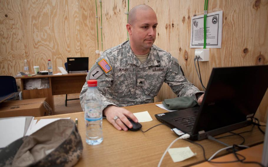 Sgt. Bart Khan, a human resources specialist deployed to the U.S. transit center at Mihail Kogalniceanu Air Base in Romania, works at his desk in the center's processing tent.