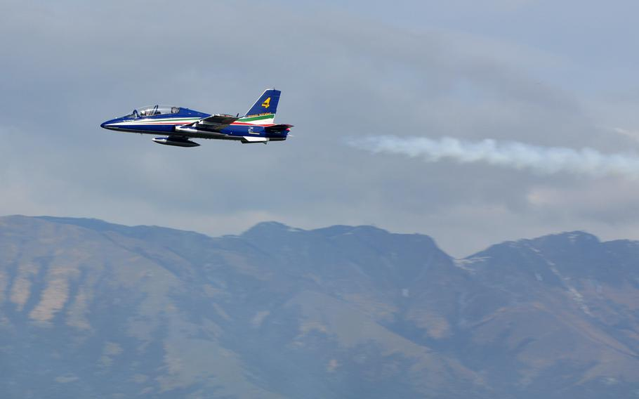 A lone member of Italy's national air acrobatics team, Frecce Tricolori, flies over Aviano Air Base on Friday, April 4, 2014, with a hazy sky over the Dolomite mountains in the background.