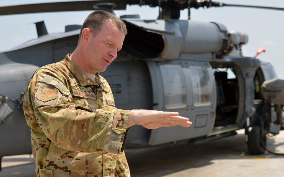 Col. Kelly Passmore, 449th Air Expeditionary Group commander at Camp Lemonnier, Djibouti, talks about search and rescue missions while standing in front of one of his unit's  HH60 Pave Hawk helicopters, Tuesday, April 1, 2014.