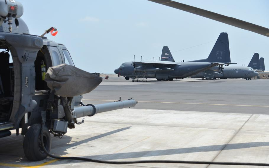 An HH-60 Pave Hawk  helicopter, left, and HC-130 and C-130 aircraft sit on the tarmac at Camp Lemonnier, Djibouti, Tuesday, April 1, 2014. The 449th Air Expeditionary Group deployed to Djibouti uses the HH-60s and HC-130s for airlift and personnel recovery missions.