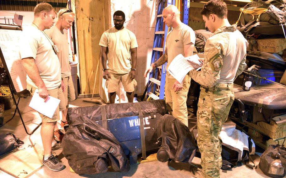 Pararescuemen of the 82nd Expeditionary Rescue Squadron at Camp Lemonnier, Djibouti, discuss the best way to prepare equipment for a mission, Thursday, April 3, 2014.