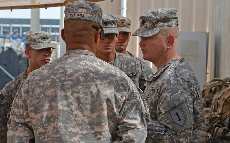 Lt. Col. Robert Magee, right, commander of 1st Combined Arms Battalion, 18th Infantry Regiment, talks with some of his soldiers at Camp Lemonnier, Djibouti, where they are deployed from Fort Riley,  Kan., Thursday, April 3, 2014.