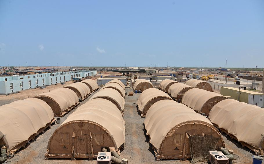 Although most tents at Camp Lemonnier, Djibouti, are no longer being used to house servicemembers, most will stay erected in case of a temporary influx of troops. At left, construction continues on one of the base?s first hard cover barracks buildings. In the distance is a swath of land in the middle of the military?s 500-acre footprint known respectively as the Djiboutian and French notches, which the U.S.  hopes to eventually incorporate into Camp Lemonnier.