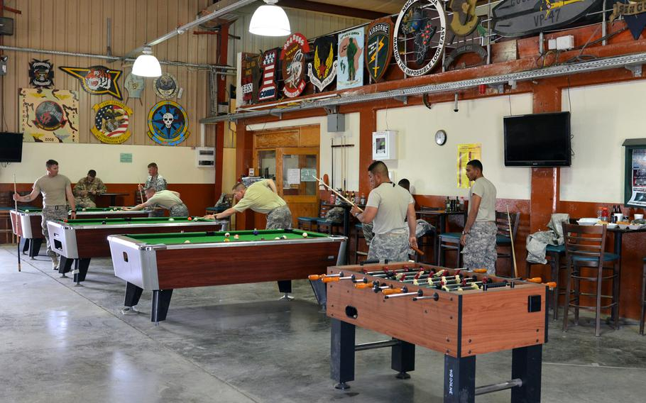 Servicemembers play pool inside 11 Degrees North, an all-ranks bar/recreation center at Camp Lemonnier, Djibouti, April 1, 2014.