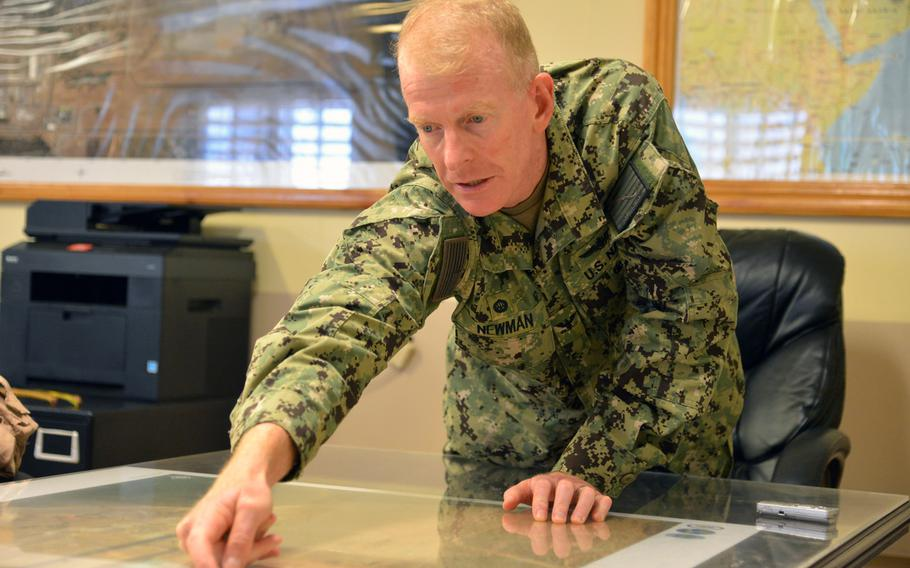 Navy Capt. Michael S. Newman, commander of base facilities at Camp Lemonnier, Djibouti, points to construction projects on a map of the base.
