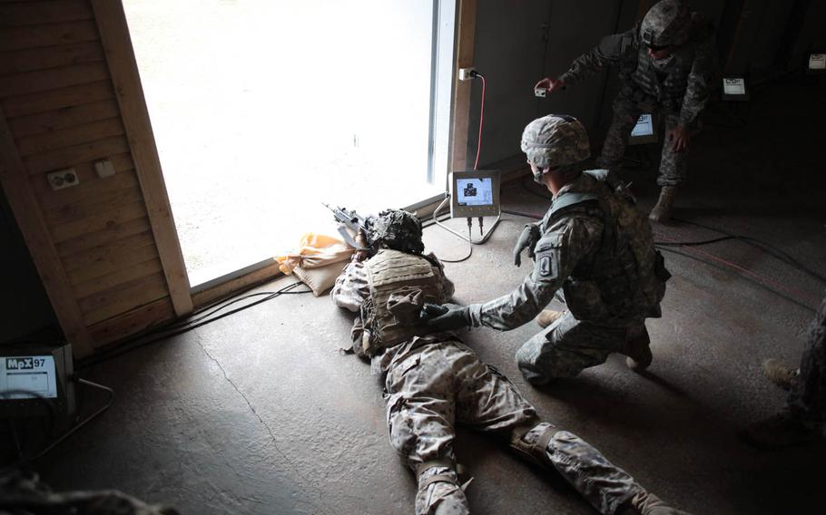 """After running a quarter mile in a gas mask and dragging a """"casualty"""" hundreds of yards, a Latvian soldier fires a rifle at a target hundreds of yards away Wednesday, April 30, 2014, as part of a shooting exercise meant to simulate the stress of battlefield conditions and build teamwork between American and Latvian soldiers."""