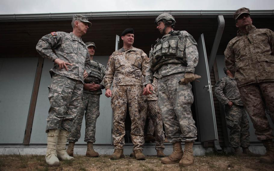 Lt. Gen. Donald Campbell Jr., left, the commander of U.S. Army Europe, speaks Wednesday, April 30, 2014, with the commander of an American rifle company and the commander of a Latvian army brigade, who are conducting joint training exercises outside of Riga, Latvia, which is roughly 120 miles from the Russian border.