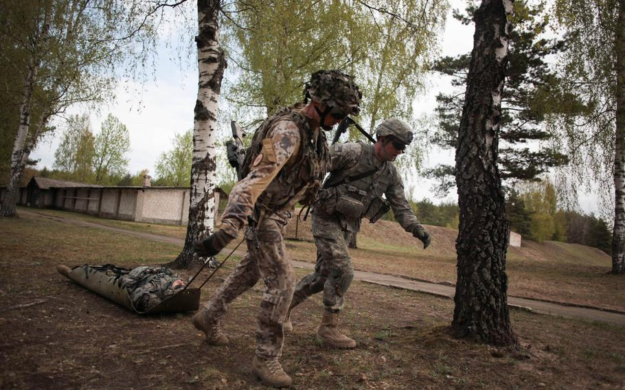 """A Latvian and an American soldier drag a """"casualty"""" Wednesday, April 30, 2014, during a shooting exercise designed to build camaraderie between the soldiers while putting them under extreme stress to simulate battlefield conditions."""