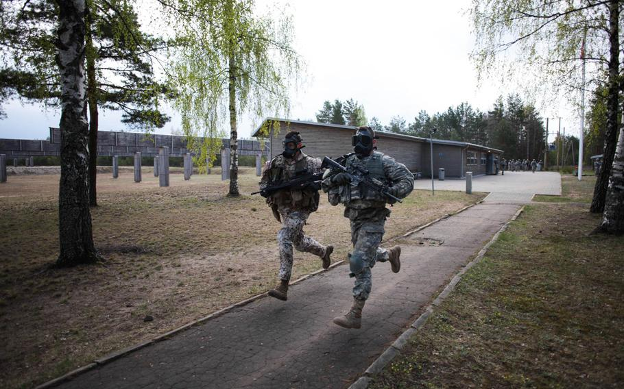 An American and a Latvian soldier sprint in full gear and gas masks at the start of a stress shooting competition on Wednesday, April 30, 2014, meant to build camaraderie and test their endurance and marksmanship under simulated battlefield conditions.
