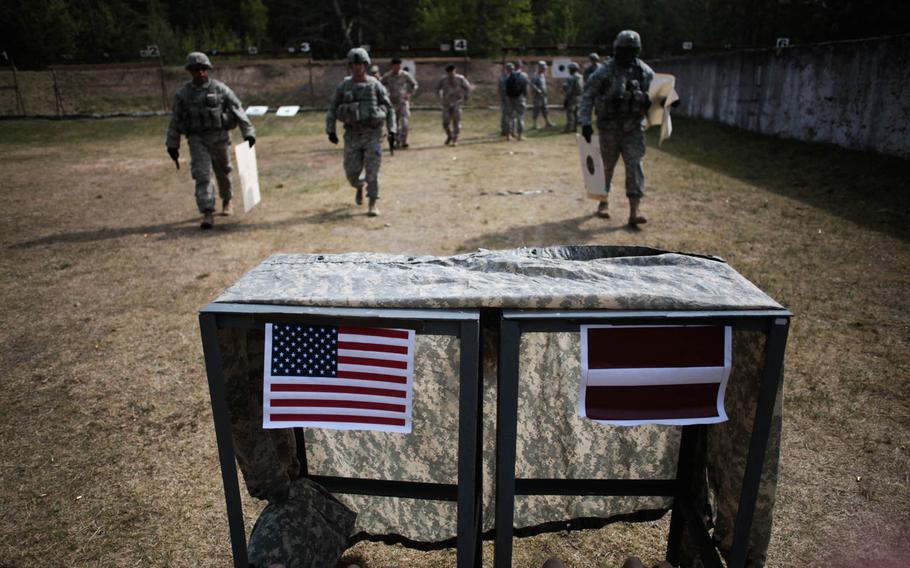 An American and a Latvian flag are taped to a table at a pistol range Wednesday, April 30, 2014, in Adazi, Latvia, where U.S. and Latvian soldiers are conducting joint training.