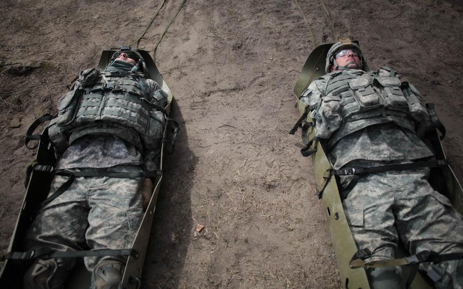 """A pair of American soldiers wait to be dragged as """"casualties"""" Wednesday, April 30, 2014, during a team-building exercise with Latvian soldiers."""