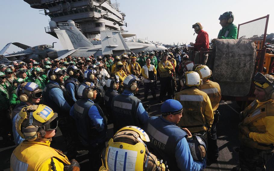 Sailors aboard the aircraft carrier USS Nimitz attend a safety brief prior to flight deck drills in the Gulf of Oman on Nov. 4, 2009.