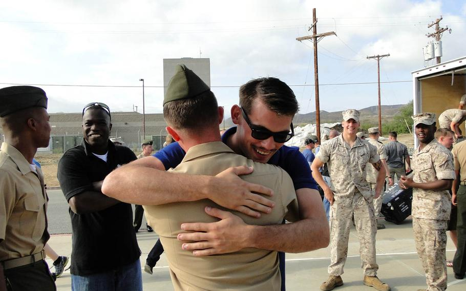 Cpl. Jeremy Schacht hugs a fellow Marine on Friday, May 23, 2014, at Camp Pendleton, California, before leaving for a deployment to Afghanistan. This is Schacht's second deployment there; he said he extended his contract so he could deploy again with the new Marines in his unit.