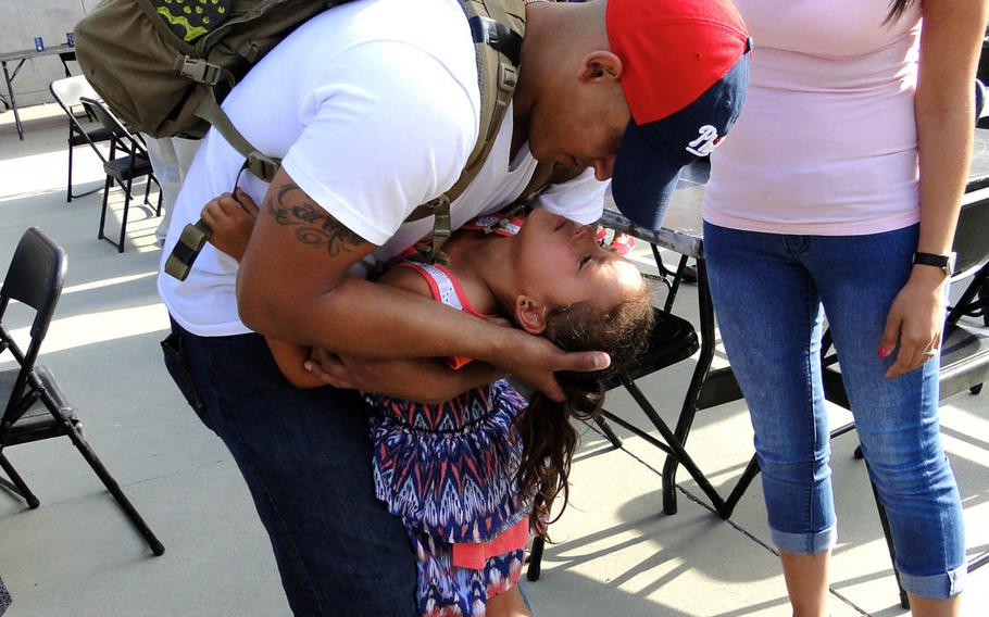Sgt. Carmelo Sierra says goodbye to his daughter, Juliana, and his wife, Obdulia Sierra, at Camp Pendleton, California, on Friday, May 23, 2014, as he leaves on a deployment to Afghanistan. This is Sierra's fourth deployment; Juliana was just two years old when he left for his first.