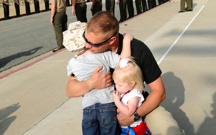 Capt. Benjamin Reading hugs his children, Liam and Zoey, goodbye before leaving on a deployment to Afghanistan with 1st Air Naval Gunfire Liaison Company from Camp Pendleton, Calif. on Friday, May 23, 2014. The unit is planning on a seven-month deployment.