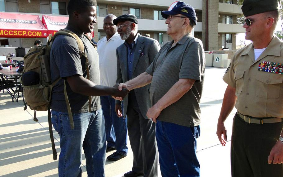 A Marine with 1st Air Naval Gunfire Liaison Company shakes hands with veterans who served in the unit in Korea and Vietnam. The Marine then boarded a bus Friday, May 23, 2014, at Camp Pendleton, California, for his own deployment to Afghanistan.