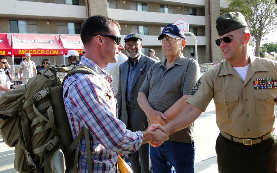 A Marine with 1st Air Naval Gunfire Liaison Company shakes hands with veterans and unit leaders. The Marine then boraded a bus Friday, May 23, 2014, at Camp Pendleton, California,  for his deployment to Afghanistan.