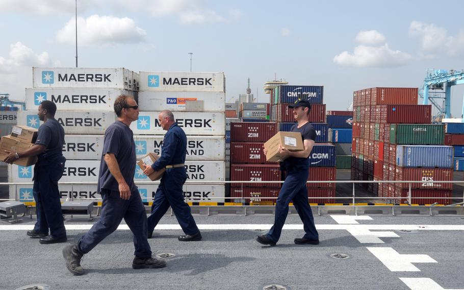 Sailors and civilian mariners with the Navy catamaran USNS Spearhead unload a cargo container of food provisions before pushing off from Lagos, Nigeria, on April 17, 2014. With too few warships to meet the demands of combatant commanders, the Navy is increasingly turning to civilian and contract mariners with the Military Sealift Command to accomplish its missions.