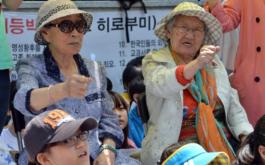 Bok-dong Kim, left, and Won-ok Gil chant during a protest a protest across the street from the Japanese Embassy in Seoul, South Korea, on May 21, 2014. Both women were forced into prostitution by Japan during World War II.