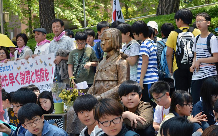 Korean protesters sit around the Pyeonghwa-bi, Peace Monument, across the Japanese Embassy in Seoul, South Korea, on May 21, 2014. A protest is held every Wednesday over the issue of Korean women forced into sexual slavery by Japan during World War II.