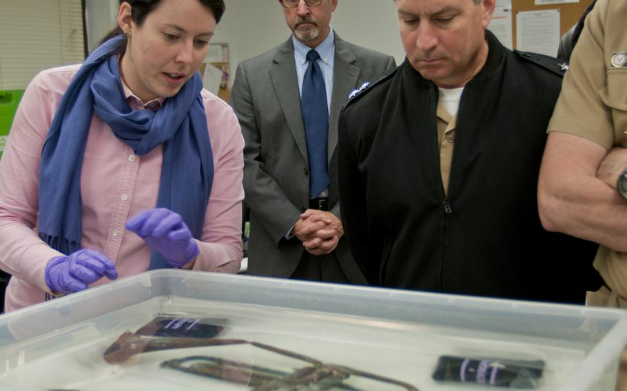Kate Morrand, archaeologist in charge of preserving the Houston trumpet, left, shows off the horn to Rear Adm. Kevin Donegan, right, during a tour of command facilities on April 29, 2014.
