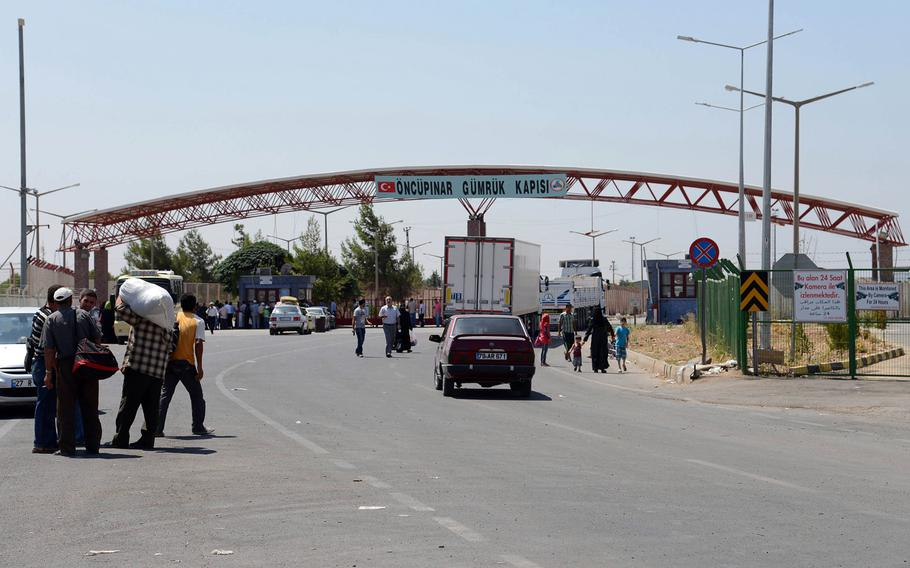 Pedestrians and vehicles travel between Syria and Turkey at the border crossing at Kilis, Turkey, in August 2013. Since the start of the civil war in Syria in 2011, scores of young men from Europe and the United States have slipped into Syria through Turkey.