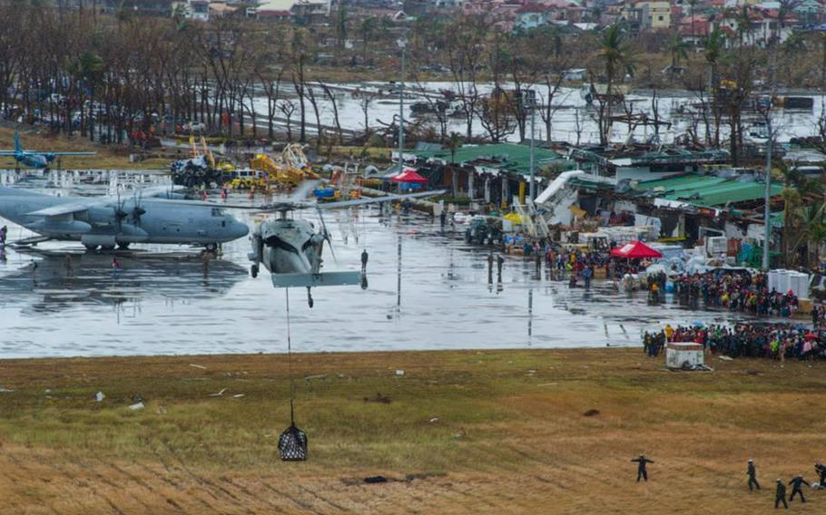 An MH-60S Sea Hawk helicopter from the Island Knights of Helicopter Sea Combat Squadron 25 drops supplies onto Tacloban Air Base in support of Operation Damayan in November 2013 in the days after the island was hit by Typhoon Haiyan.
