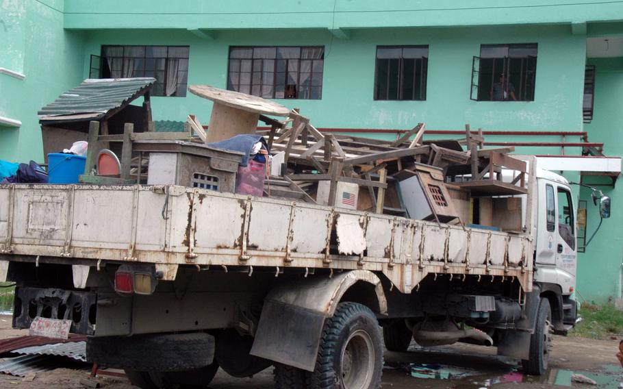 A truck carries typhoon victim's possessions away from a recently vacated camp that served as a home for many Filipinos for the last eight months.