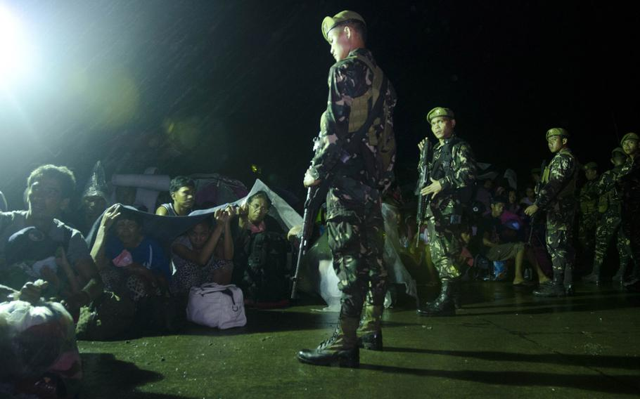 Filipino Army guards maintain order among a group of typhoon victims waiting to board a flight out of Tacloban Airport bound on Nov. 15, 2013.