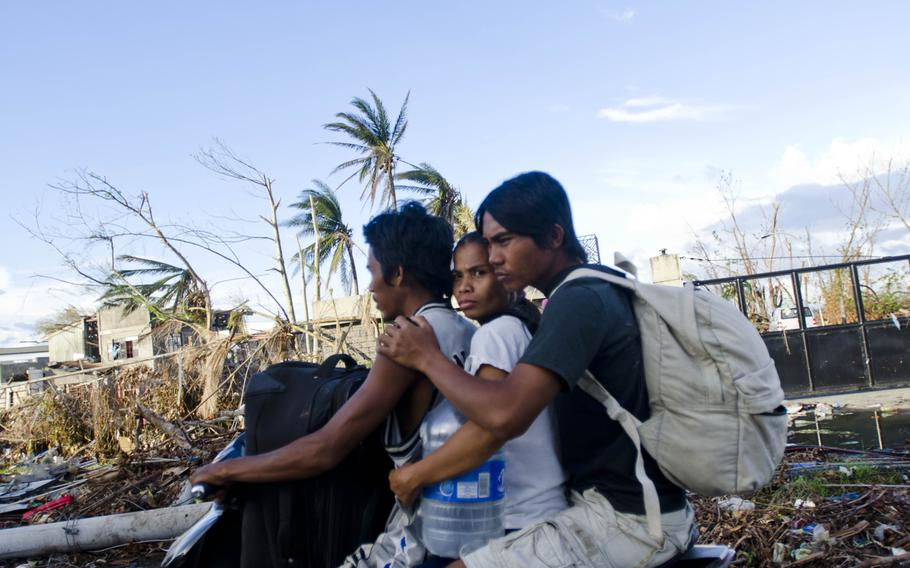 Victims of Typhoon Haiyan ride through the rubble in Tacloban in November 2013, nearly two weeks after the disaster struck their city.