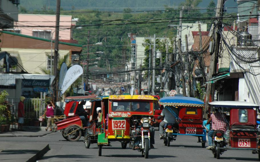 Traffic clogs a downtown street in Tacloban. Eight months after Typhoon Haiyan, business is booming for tradesmen helping to repair storm-damaged homes and buildings.