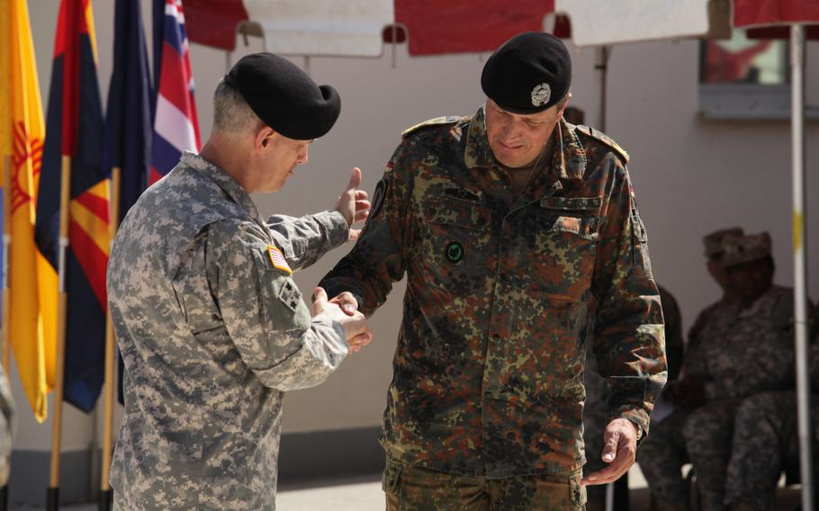 U.S. Army Europe commander Lt. Gen. Donald M. Campbell Jr., left, and German Brig. Gen. Markus Laubenthal, USAREUR's new chief of staff, shake hands after Campbell put a USAREUR patch on Laubenthal's uniform to formally welcome him as the command's first non-American chief of staff on Aug. 28, 2014.