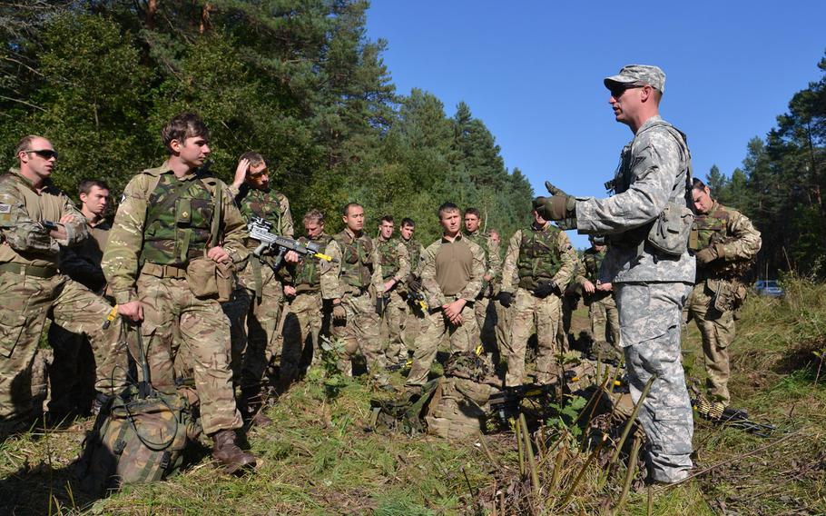 Sgt. 1st Class Josh Ward of the Joint Multinational Readiness Center discusses with British soldiers things done right and wrong during convoy training at Exercise Rapid Trident near Yavoriv, Ukraine, Wednesday, Sept. 17, 2014.