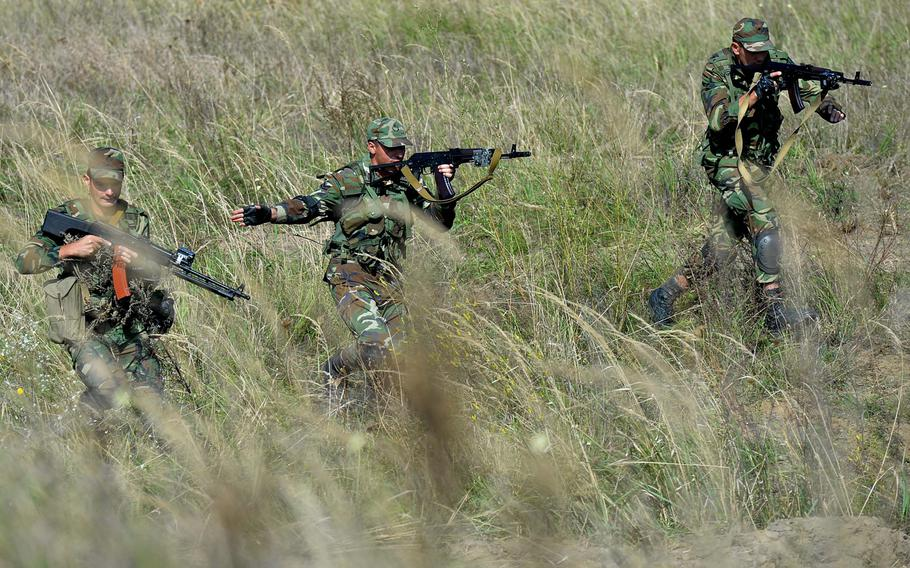 Soldiers from Azerbaijan make their way through tall brush as they go through patrol training during Exercise Rapid Trident near Yavoriv, Ukraine, Wednesday, Sept. 17, 2014. The exercise runs through Sept. 26.