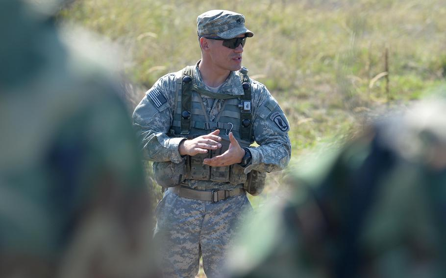 Staff Sgt. Byron Prohovich of the 173rd Airborne Brigade talks to soldiers from Azerbaijan after instructing them in patrol tactics at Exercise Rapid Trident near Yavoriv, Ukraine, Wednesday, Sept. 17, 2014.