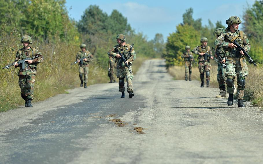 Romanian soldiers patrol a road during Exercise Rapid Trident near Yavoriv, Ukraine, Thursday, Sept. 18, 2014. The U.S., Ukraine and 13 other nations are taking part in the exercise.