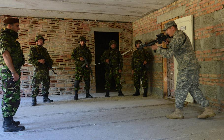 Staff Sgt. Julio Ortiz, right, of the 173rd Airborne Brigade, gives Romanian soldiers pointers on room-clearing during cordon-and-search training at Exercise Rapid Trident near Yavoriv, Ukraine, Thursday, Sept. 18, 2014.