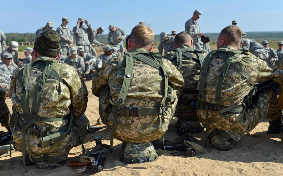Ukrainian army cadets sit on their helmets during a break at Exercise Rapid Trident near Yavoriv, Ukraine, Wednesday, Sept. 17, 2014. In the background are soldiers from the U.S. Army's 173rd Airborne Brigade.