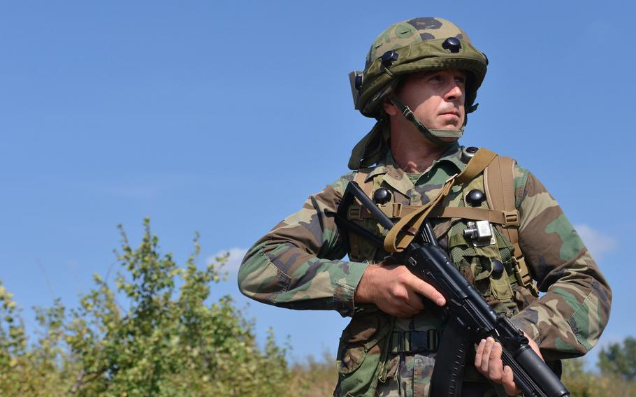 A Romanian soldier patrols a road during training at Exercise Rapid Trident near Yavoriv, Ukraine, Wednesday, Sept. 17, 2014.